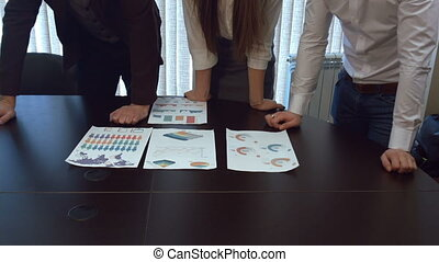 Hands work with financial documents.
