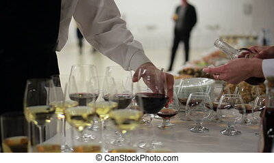 waiter pouring brandy into glasses at a reception