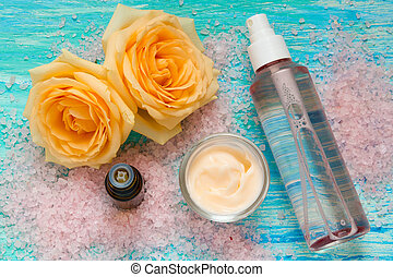 cosmetic products from rose, cream and a bottle of rose water, essential oil, flowers on turquoise wooden background