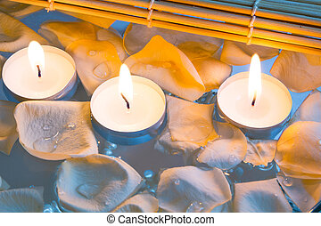 Spa still life with candle and rose petals over bright...