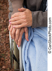 closeup of women hands, one of them in a wheelchair