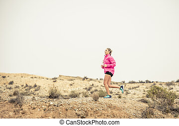young sport woman running off road trail dirty road with dry desert landscape background training hard