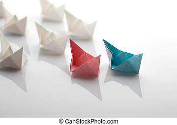 Leadership concept using blue paper ship among white