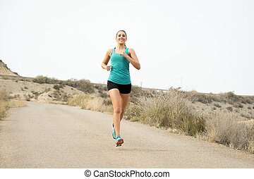 sport woman running on asphalt dirty road with dry desert landscape background training hard