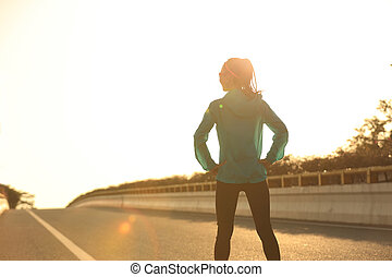 fitness young woman runner standing with her hands on hips...