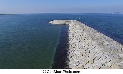 aerial flying breakwater of stone - aerial drone flying...
