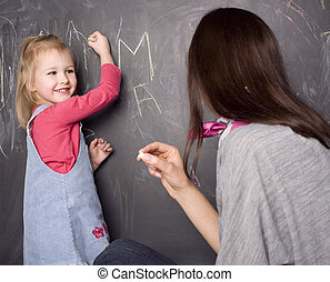 little cute pupil girl with teacher in classroom writing on blackboard