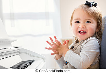Happy smiling toddler girl excited to play piano - Happy...