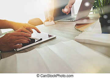 two colleagues interior designer discussing data and digital tablet and computer laptop with sample material on wooden desk as concept