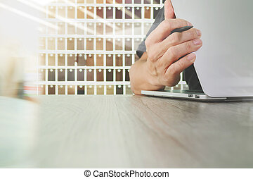 interior designer hand working with laptop computer and sample material on wooden desk as concept