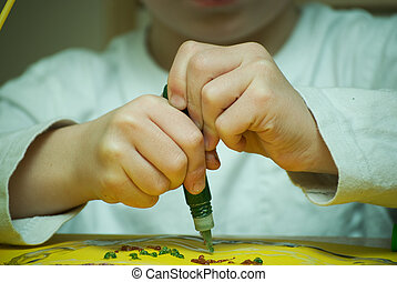 child\'s hands drawing with glitter glue.