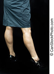 woman showing off shapely legs over a black background.