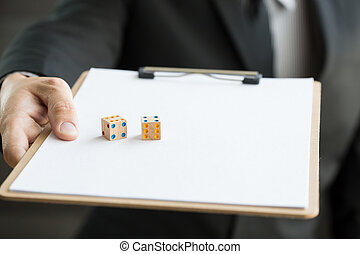 Businessman with two dices on white document.