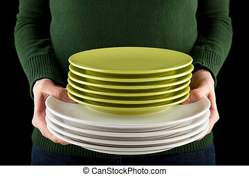 hands holding a pile of green and white dishes - female...
