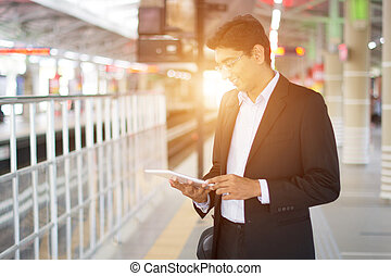 indian business male using tablet computer while waiting for...