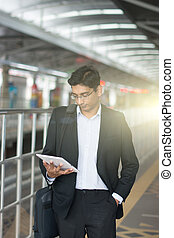 india male using tablet computer at train station