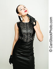 sexy young woman in black leather dress with braided hair is holding a gun. woman aiming his chin
