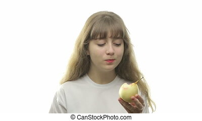 Teenage girl eating a pear on white background
