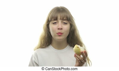 Young blond girl eating a pear on white background