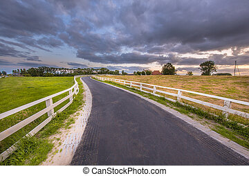 Curved Asphalt country road with white fences