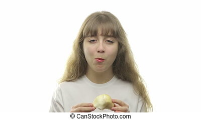 Blond teenage girl eating a pear on white background