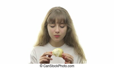 Teenage girl bites off pear on white background