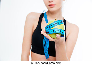 Apple with blue measuring tape holded by sportswoman -...
