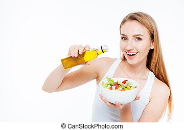 Woman poured oil into salad - Cheerful young woman poured...