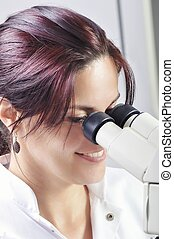 Young scientist studying new substance or virus in microscope