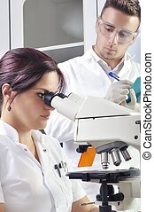 Young scientists studying new substance or virus in microscope