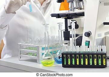 Scientist studying new substance or virus in microscope