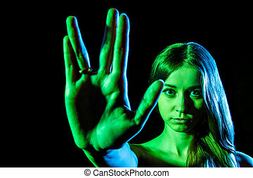 Beautiful young woman in green light showing the alien sign...