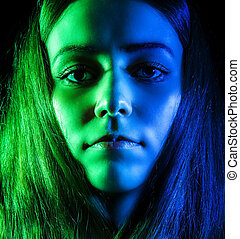 Beautiful young woman in green and blue lights over black...