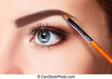 Beautiful female eyes with bright blue make-up and brush on...