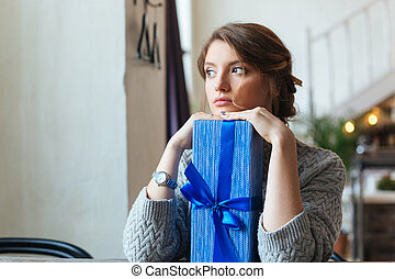 Woman sitting at the table with gift box - Thoughtful woman...