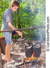 Boy cooking on campfire - Young boy cooking camp food in...