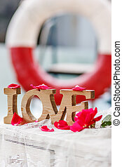 """Carved wood word """"Love"""" among pink rose petals on the..."""