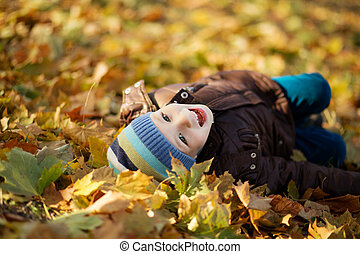 Portrait of a cheerful little boy wallow in fall foliage....