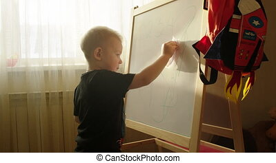 Boy Wiping off Scribbles from the Marker Board - Little boy...