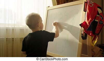 Boy Erasing Written from the Marker Board - Little boy is...