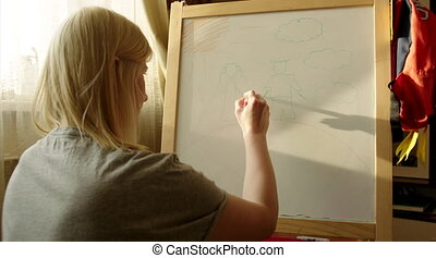 Woman Drawing Happy Family on Marker Board - Young woman is...