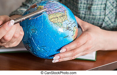 Female hand with  pen and a globe of the puzzle