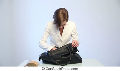 girl searching for a phone in her bag - girl searching for a...