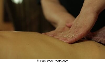 Masseur makes massage with oil for girl.