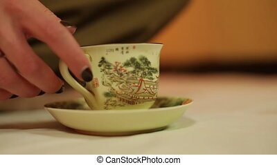 Girl drinks tea from a cup with a Chinese pattern