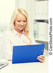 smiling businesswoman with clipboard in office
