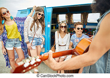 happy hippie friends playing music over minivan - summer...