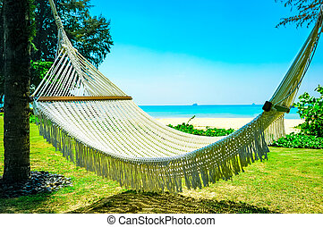 Hammock between two palm trees on the beach