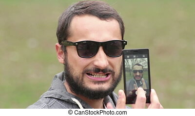 man photographing himself on a mobile phone
