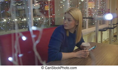 Young Woman in Cafe Looking Out for Her Friend - Young woman...